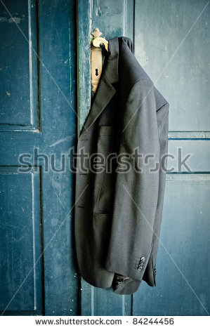 stock-photo-mans-coat-hanging-on-a-handle-of-a-vintage-door-84244456